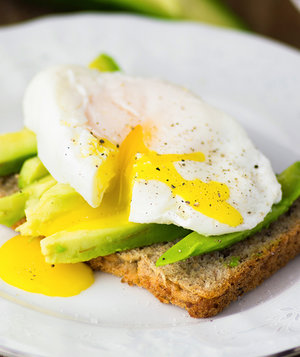 Close up of delicious fresh poached egg with avocado and healthy toast breakfast