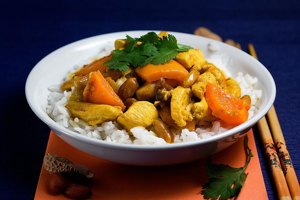 A plate of curried chicken, bell peppers, and nuts