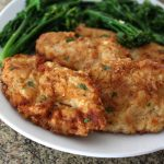A pair of fried chicken breasts with collared greens
